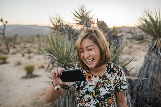 A young Asian woman laughs while looking at a picture on her phone in Joshua Tree National Park.