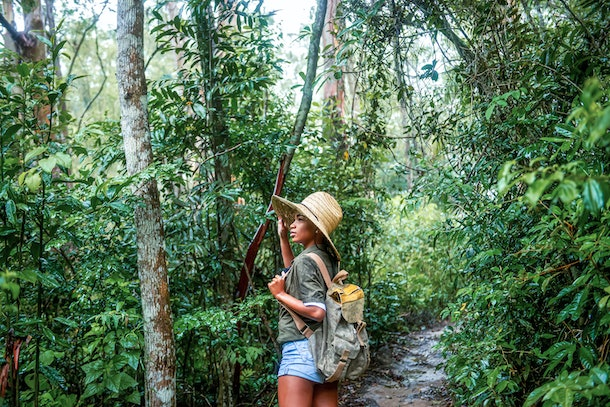 A young Black woman stands amongst lush trees while on a hike in a national park.