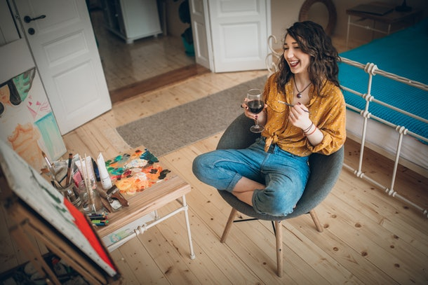 A happy woman paints a canvas with a glass of wine in hand, while sitting in her bedroom.