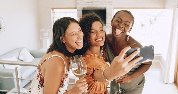 Three best friends smile for a selfie, while holding wine in their hands.