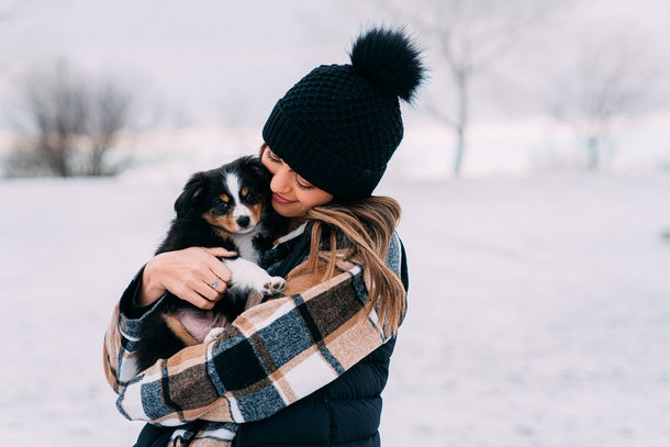 A happy woman bundled up for winter hugs her puppy in the snow.