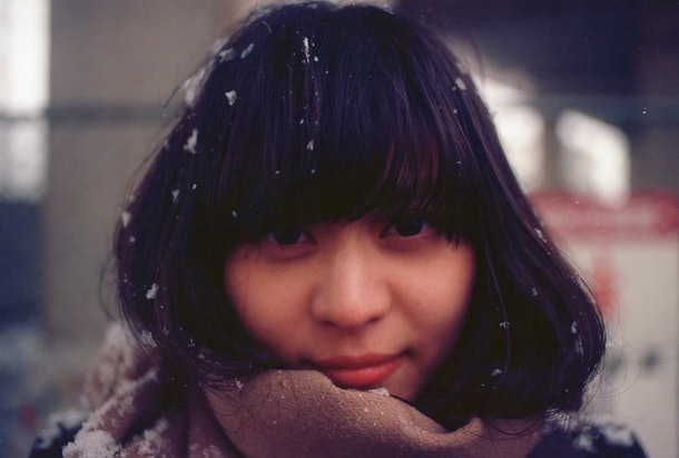 A woman in black bangs smiles at the camera with a snow peppering her hair.