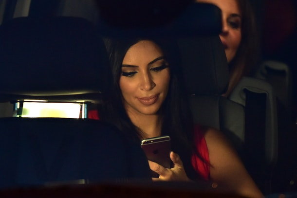 Kim Kardashian looks at her iPhone while sitting in the car.