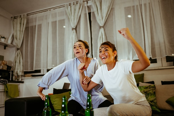 Two women cheer while watching the Super Bowl on their couch and doing face masks.