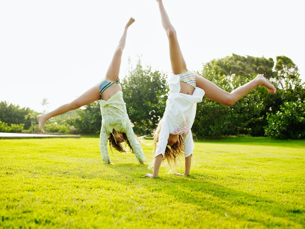 Two women cartwheel over a lawn to enjoy the sunny days.