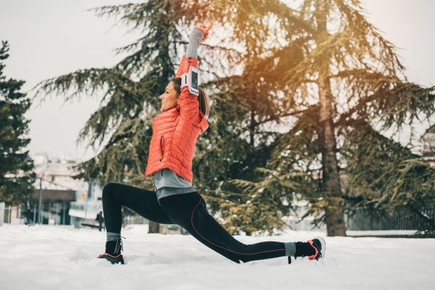A young woman does winter-themed yoga in her backyard while wearing activewear.