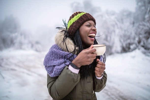A happy woman laughs while enjoying a cup of hot chocolate outside on a snow day.