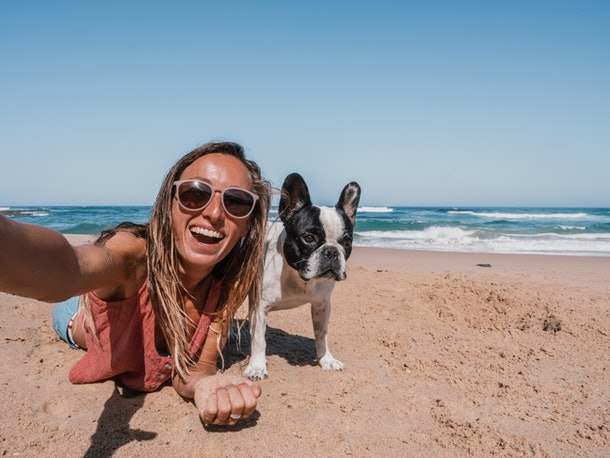 A happy woman takes a selfie with her dog at the beach.