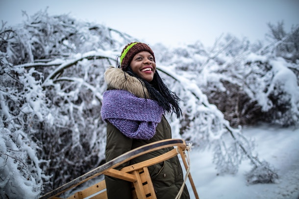 A happy woman all bundled up to brave the snow holds a sled and smiles.