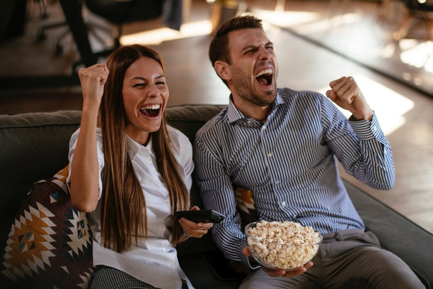 A young couple cheers while eating popcorn and watching the Super Bowl 2021 Halftime Show.