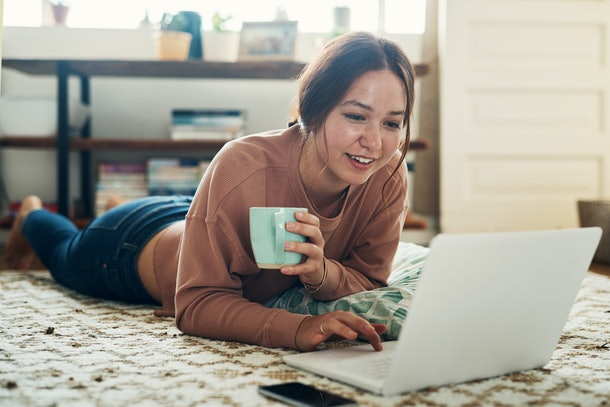 A woman sipping tea lays down on the floor for a cozy Zoom call with a best friend.