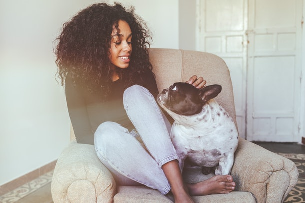 A young woman pets her dog while sitting in a comfy chair.