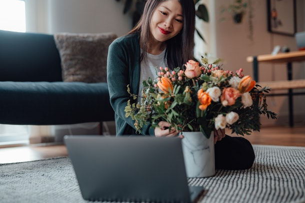A smiling woman sits in front of her laptop with a beautiful bouquet of flowers while on a virtual Valentine's Day date.