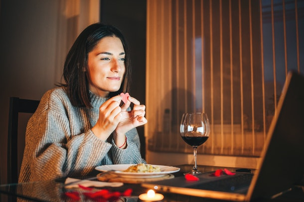 A cozy woman holds a paper heart to her laptop in front of wine and dinner while on a virtual Valentine's Day date.