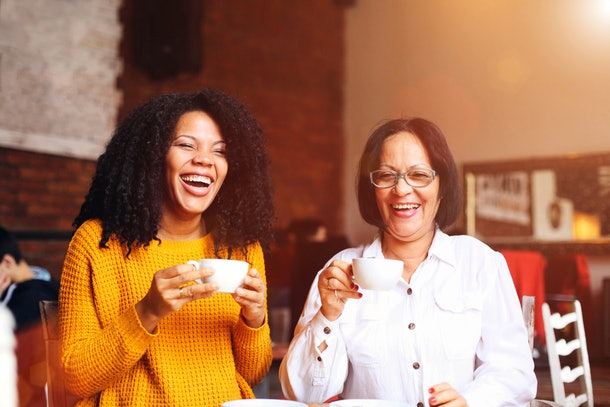 A mother and daughter enjoy coffee at a café while laughing.