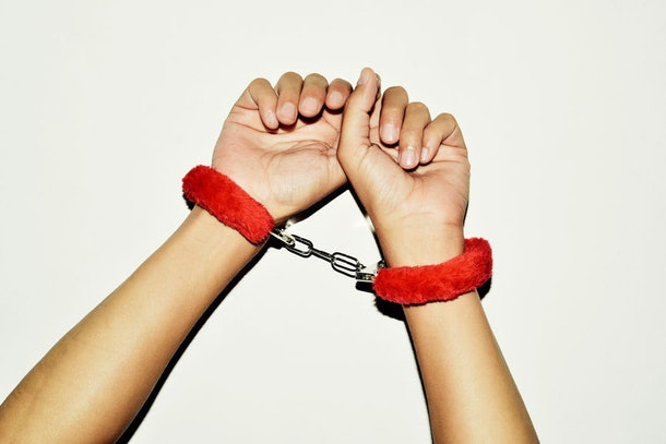 Fuzzy red handcuffs on hands.