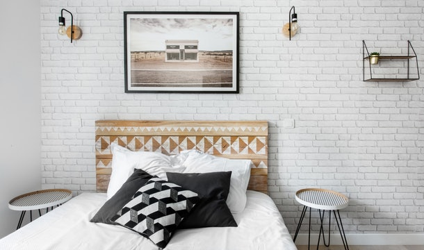 A trendy studio apartment in Paris on Airbnb has a bed with black and white pillows and wooden accents.