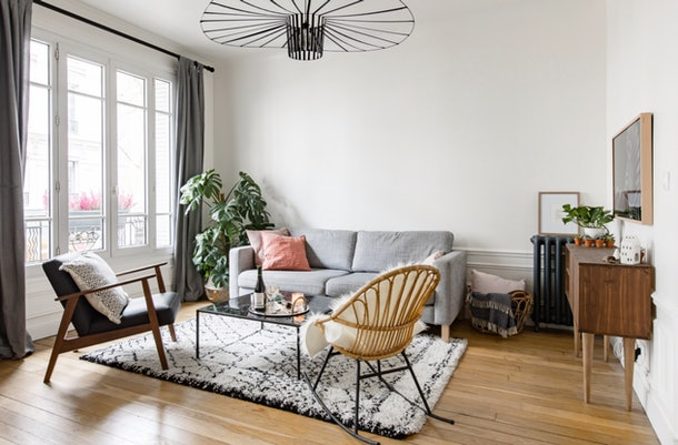 A stylish apartment you can stay in in Paris has a grey couch, modern decor, and a historical atmosphere.