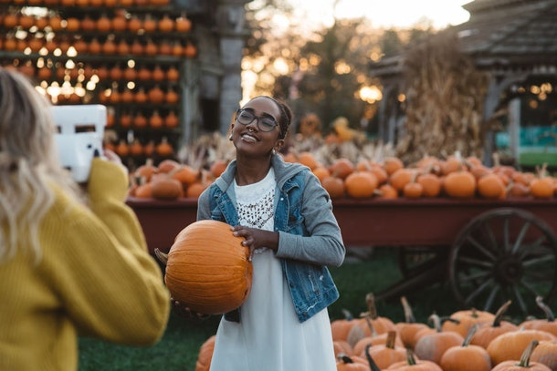 A girl in a white dress and jean jacket is posing for her best friend in a pumpkin patch for Halloween.