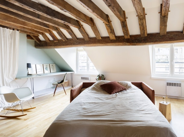 A cozy bed with a pink pillow in a loft in Paris is where you should relax on your next trip.