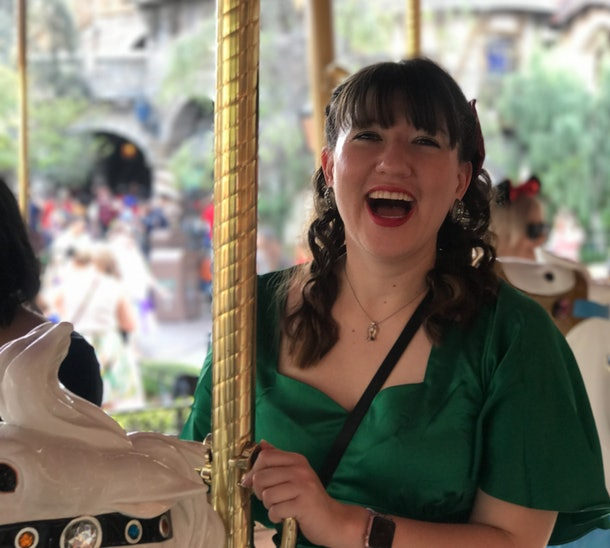 A woman smiling on the carousel at Disney, which is a perfect Disneyland activity for couples to do.