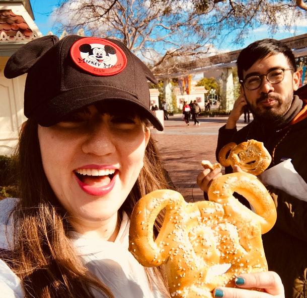 a woman and man eating Mickey pretzels at Disney is always a fun Disneyland activity for couples.