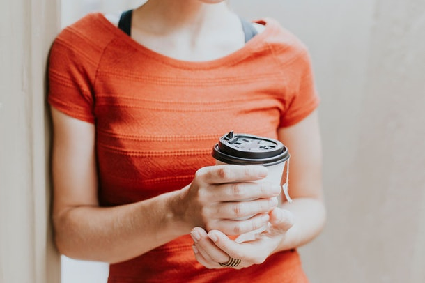 A girl is holding a latte in a to-go cup and wearing an orange shirt.