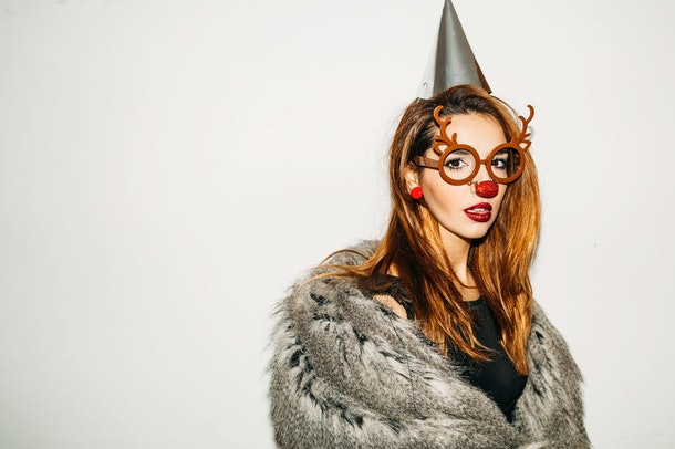 A girl is dressed up like a reindeer with antlers, a furry coat, and glasses on Halloween.