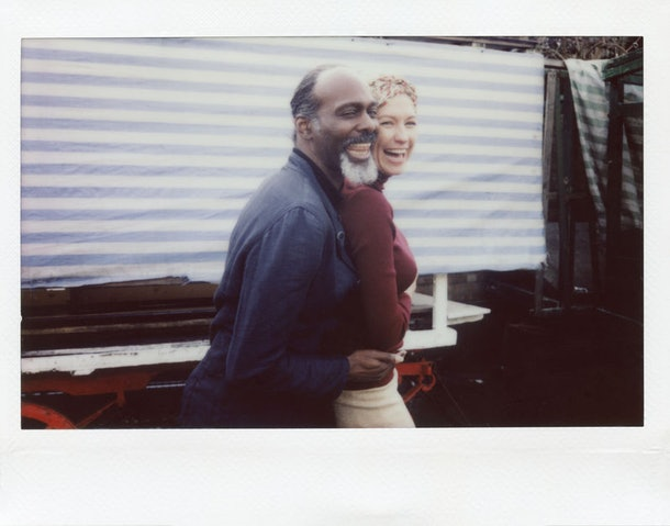 A couple is laughing and embracing the outdoors while somebody takes their picture on a Polaroid camera.