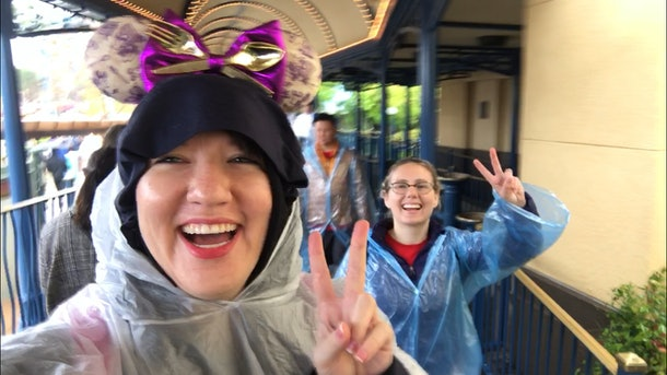 Two friends waiting in line at Disney wearing rain ponchos and holding up peace signs.