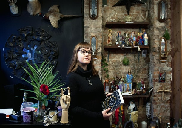 A brunette woman dressed in a black sweater and glasses holds a book on black arts in a studio.