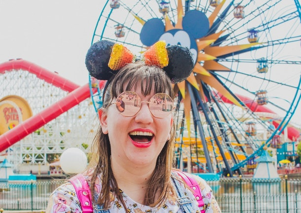 A woman laughs at the camera in a pair of sunglasses, Minnie ears, and a hot pink backpack in front of a Ferris wheel at Disney.