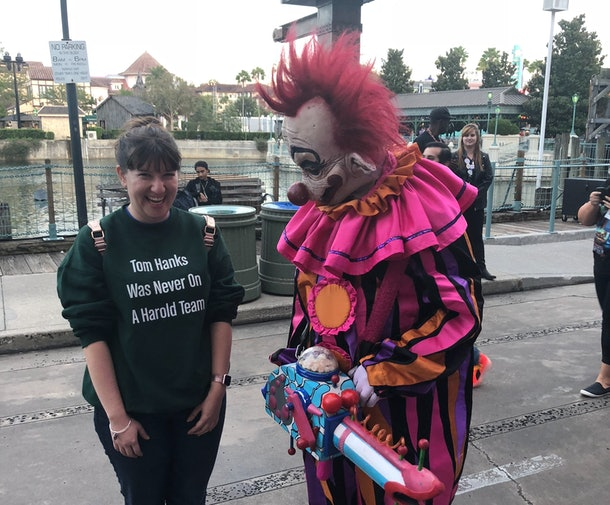 """A woman laughs and poses next to a """"Killer Klown"""" from the 'Killer Klowns from Outer Space' movie at Halloween Horror Nights."""