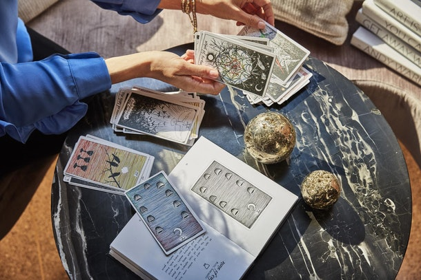 A woman reads tarot cards on a black marble table.