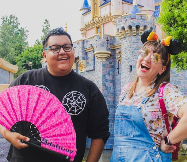 Two friends are standing in front of the Disneyland castle, one holding a pink fan and the other smiling with her Minnie ears and Disney backpack.