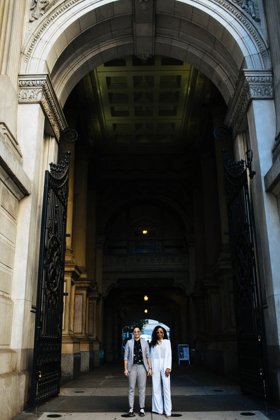 A newly-married couple is standing under an arch in the city in chic clothes and holding hands, smiling at the camera.