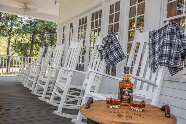 A row of white rocking chairs line the front porch of the historic home on the Jim Beam American Stillhouse distillery grounds.