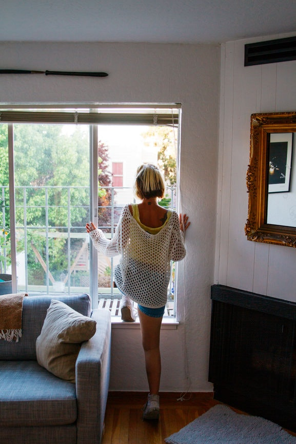 A woman with blonde, short hair is standing in the window of a cozy apartment.