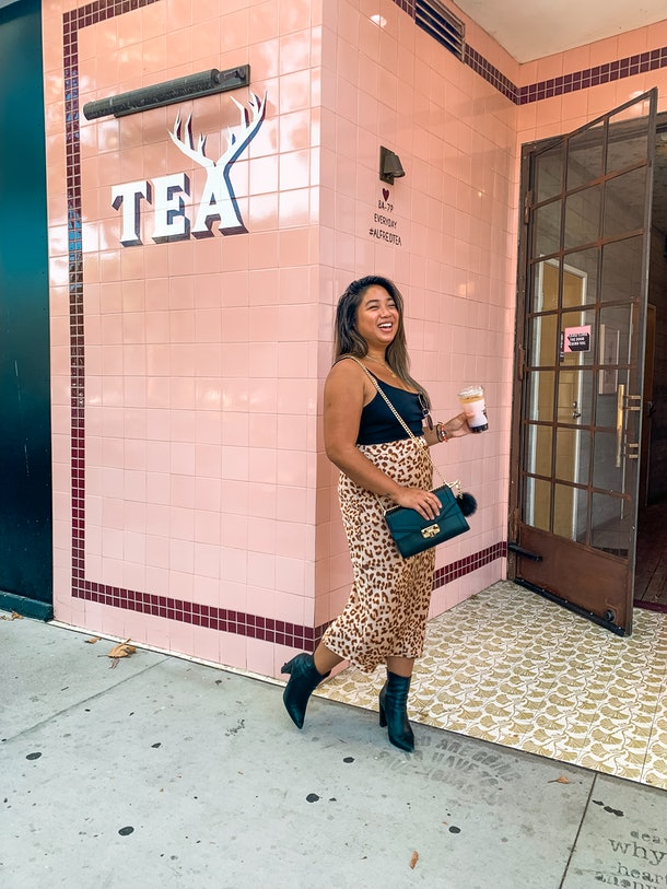 Woman in pair of black booties, leopard skirt, and black tank top laughs while holding her coffee cup in front of a coffee shop in LA.