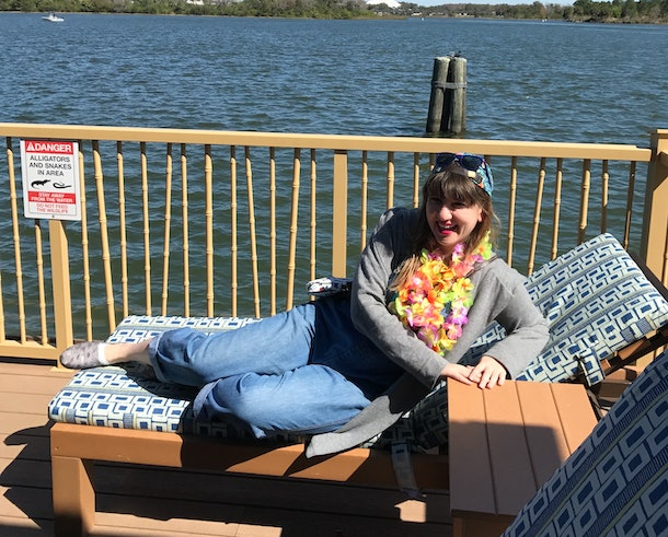 A brunette woman relaxing on the deck of a Disney bungalow on a sunny day.