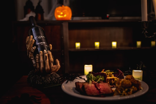 A dinner entree from Refinery's Hotel of Horrors room service menu sits on a table next to a bottle of Refinery wine.