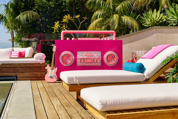 The outdoor deck at Barbie's Malibu Dreamhouse has wooden lounge chairs with white cushions, a giant pink stereo, and is surrounded by lots of palm trees.