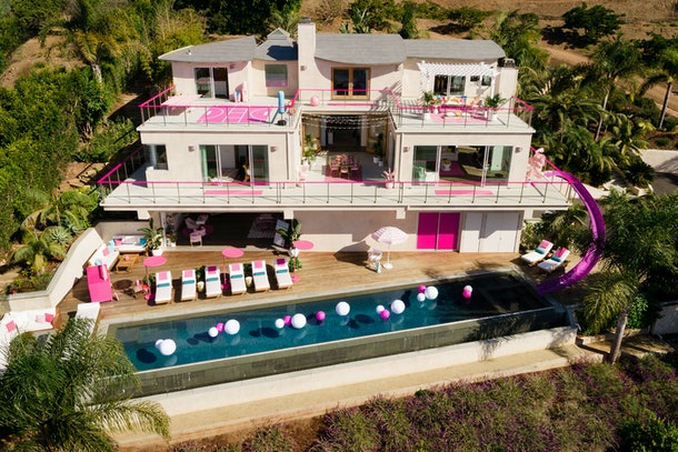 The exterior of Barbie's Malibu Dreamhouse during the day features an infinity pool, pink and white lounge chairs, and lots of other adorable hot pink details.