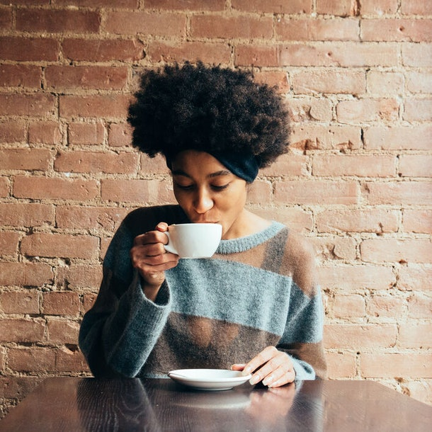 A black woman sips on hot cider in a mug in front of a brick wall at a cider mill.