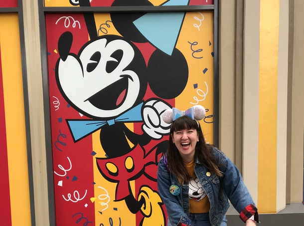 A woman wearing sequinned Minnie ears and a Disney birthday button laughs in front of a Mickey Mouse wall at Downtown Disney.