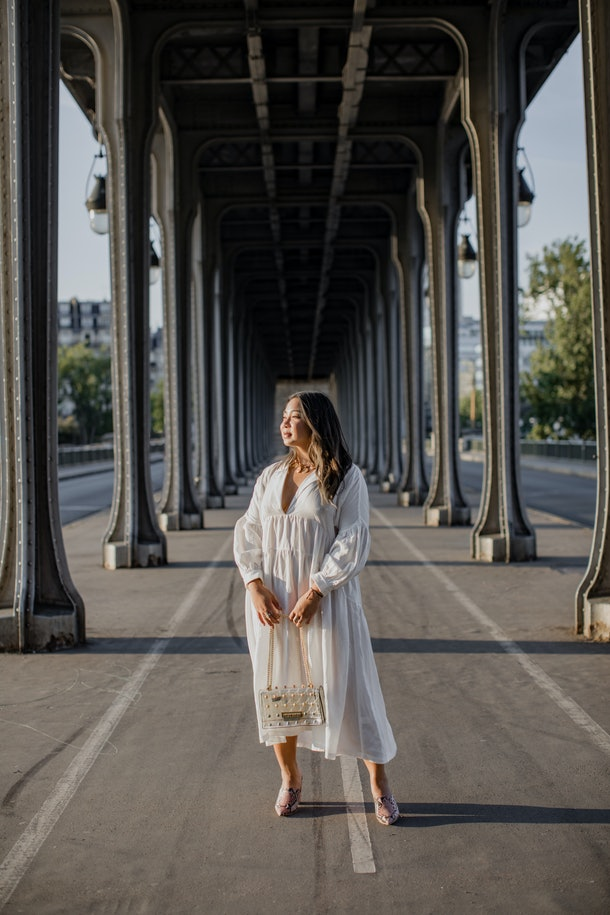A woman in white long-sleeved dress and pink shoes stands at the center of the BIr-Hakeim bridge in Paris.