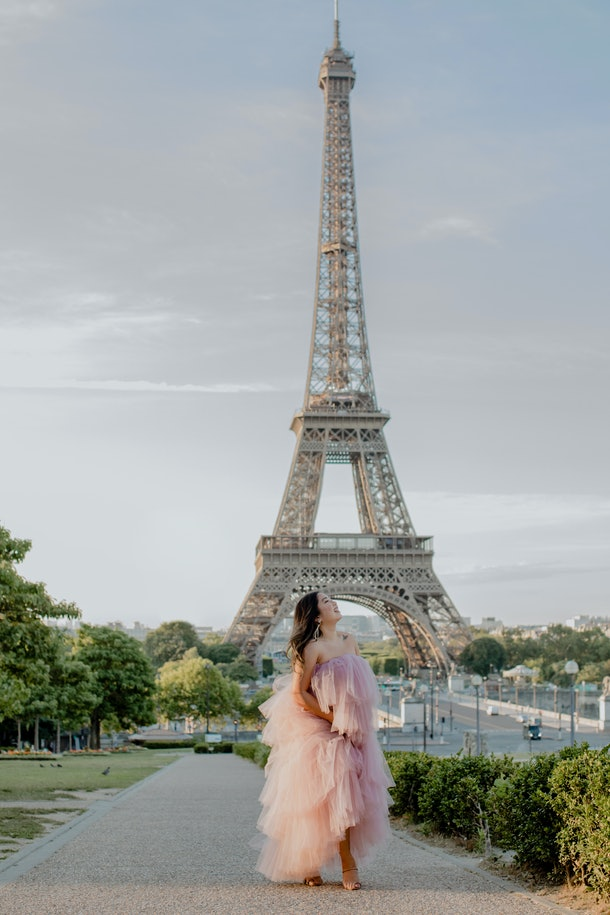 A girl dressed in a pink tulle dress smiles, looks up, and poses in front of the Eiffel Tower in Paris.