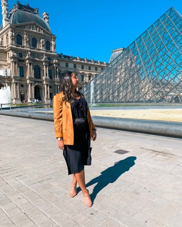A woman dressed in a black slip dress and bright yellow-gold blazer poses in front of the Louvre Pyramid.