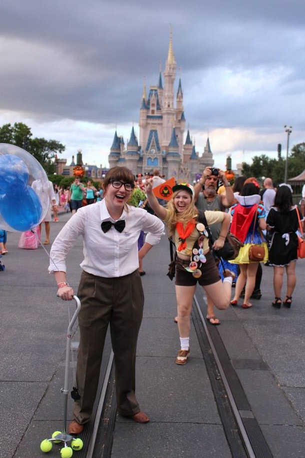 Two friends dressed like Carl and Russell from 'Up' pose for a picture in front of Cinderella's castle in Disney World.