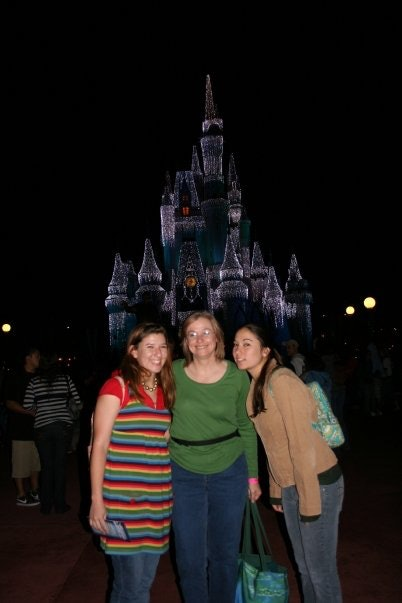 A family poses in front of Cinderella's castle in Disney World at night.